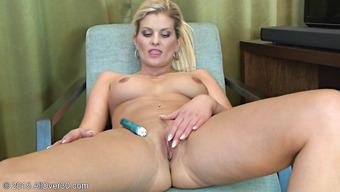 Немолодая блондинка мастурбирует киску в кресле