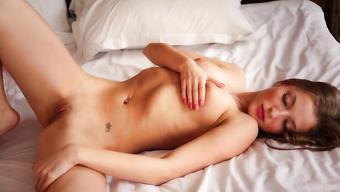 В спальне миниатюрная брюнетка показывает горячие дырочки