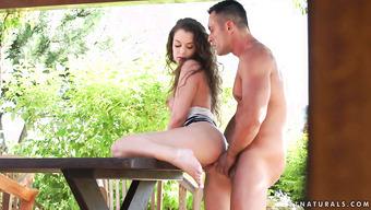 Паренек в саду жарит кучерявую подружку возле стола